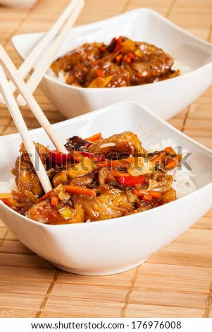 Sweet and sour pork and rice in a bowl - stock photo