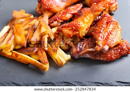 Sweet and sticky chicken wings with chips - stock photo