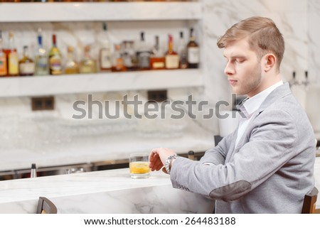Sweet anticipation of the meeting. Young handsome man in grey jacket looking at his watch and sitting at the counter of the bar - stock photo