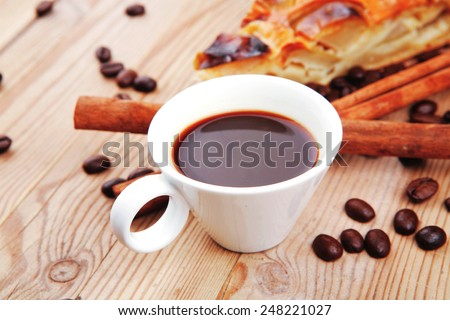 sweet apple cake with small white coffee cup and cinnamon sticks on wooden table