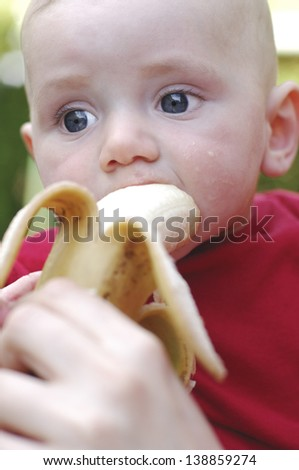 Sweet baby boy eat banana outdoor - stock photo