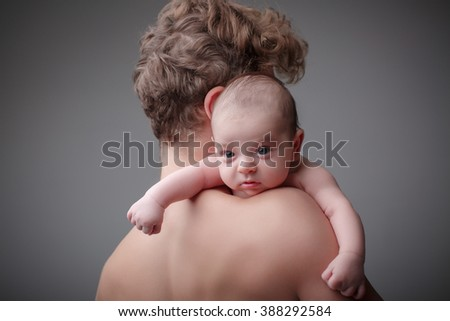 Sweet baby boy on father's shoulder on gray background - stock photo
