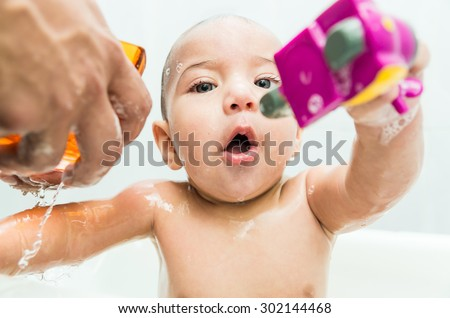 Sweet baby boy playing with toy during bath time - stock photo