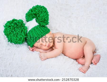 sweet  baby boy sleep in a green knitted hat - stock photo