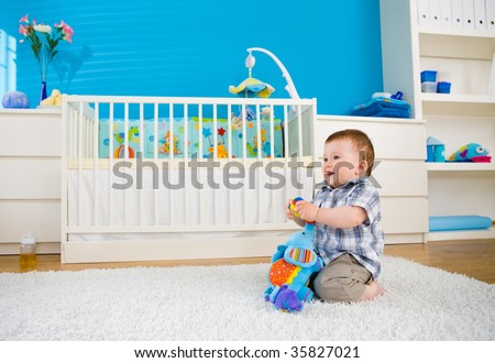 Sweet baby boy ( 1 year old ) sitting on floor at home and playing with soft toys at children's room. - stock photo