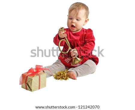 Sweet baby girl in red velvet dress and gray stretch pants inspects toy brass horn with curiosity. Wrapped holiday gift and gold bow nearby. Isolated/cut out, white background, horizontal, copy space.