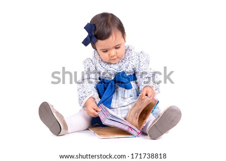 Sweet baby girl playing with a book