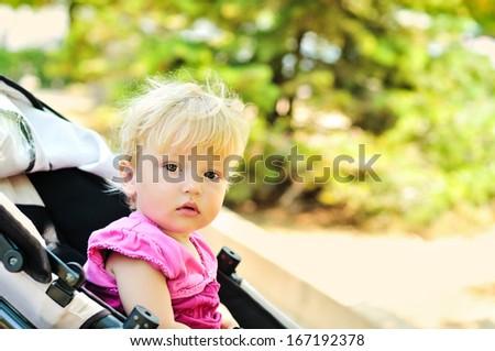 sweet baby girl sitting in stroller - stock photo