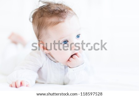 Sweet baby girl with beautiful blue eyes sucking on her fingers - stock photo