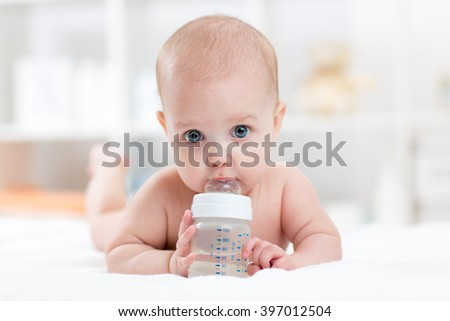sweet baby holding bottle and drinking water - stock photo