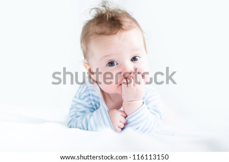 Sweet baby in a blue shirt sucking on its finger - stock photo