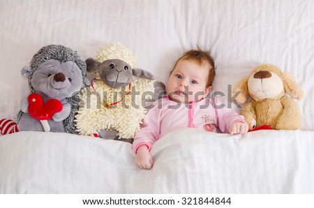 Sweet baby in bed with toys - stock photo
