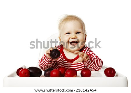 Sweet baby is sitting on chair and selecting plums. - stock photo