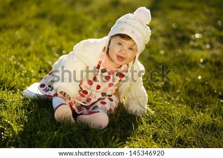 sweet baby sitting on grass in garden - stock photo