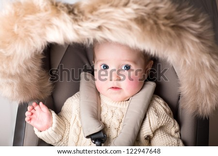 Sweet baby with big beautiful eyes sitting in a luxury fur stroller - stock photo