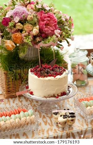 Sweet bar on summer wedding. Cake with protein cream and fresh berries on a cake stand outdoor