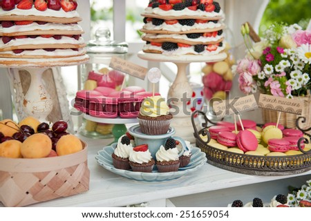 Sweet bar on summer wedding. Cupcakes and Layer cake with protein cream and blackberries and other sweets outdoors
