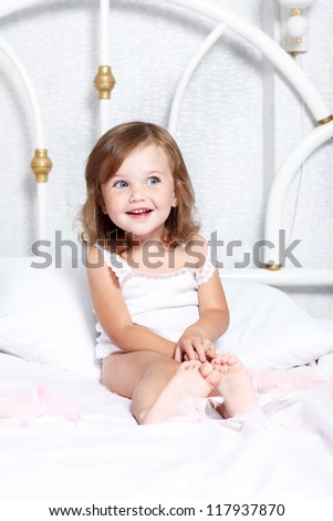 Sweet barefoot toddler girl in bed - stock photo
