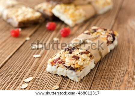 Sweet bars with a chocolate, rise and cranberry. Various granola bars on a wooden backgroung