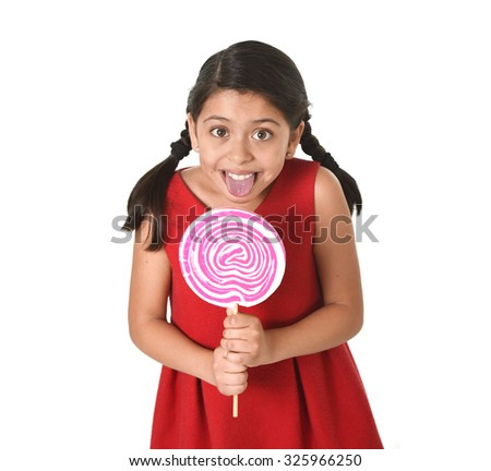 sweet beautiful latin female child holding big pink spiral lollipop licking happy  isolated on white background in funny crazy face expression and sugar addiction concept - stock photo