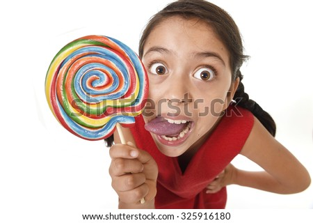 sweet beautiful latin female child with big lollipop candy eating and licking happy and excited isolated on white background with tongue out in funny crazy face expression and sugar addiction concept - stock photo