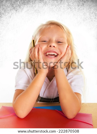 sweet beautiful little schoolgirl blonde hair and blue eyes smiling happy on school desk holding pencil posing children education concept isolated on studio lighting and background - stock photo