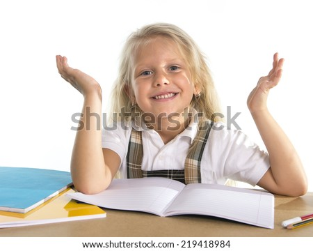 sweet beautiful little schoolgirl with blonde hair sitting happy on desk in children education concept isolated on white background - stock photo