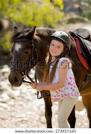 sweet beautiful young girl 7 or 8 years old holding bridle of little pony horse smiling happy wearing safety jockey helmet posing outdoors on countryside in summer holiday