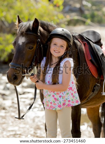 sweet beautiful young girl 7 or 8 years old holding bridle of little pony horse smiling happy wearing safety jockey helmet posing outdoors on countryside in summer holiday - stock photo