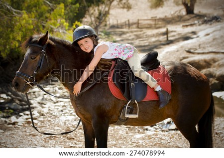 sweet beautiful young girl 7 or 8 years old riding pony horse hugging happy in  safety jockey helmet posing outdoors on countryside on summer holiday in love animal concept - stock photo