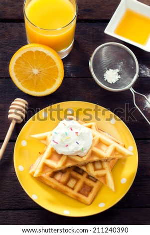 Sweet Belgian waffles with sweet cream.Selective focus on the waffles  - stock photo