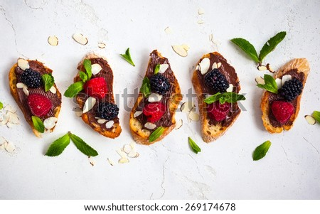 Sweet berry bruschetta with chocolate nut butter,mint and sliced almonds on the white vintage dish - stock photo