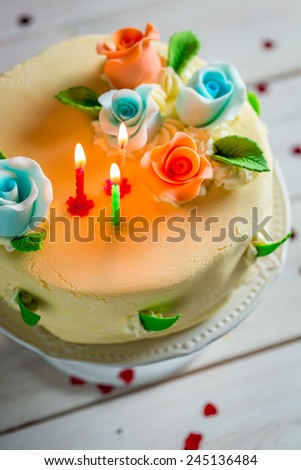 Sweet birthday cake decorated with candles and roses - stock photo
