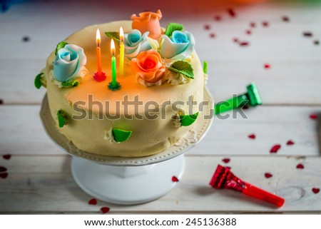 Sweet birthday cake with lighted candles and marzipan roses - stock photo