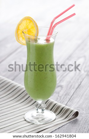 Sweet blended kiwifruit smoothie served in long glass. Fresh fruit mousse decorated with orange slice.