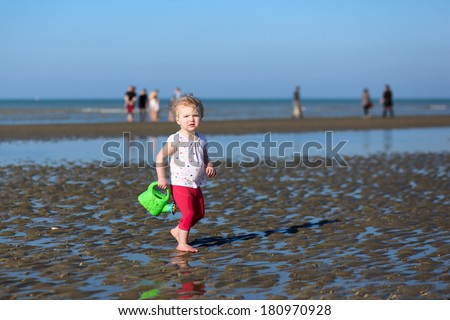 Sweet blonde little toddler girl in colorful outfit plays with watering can at a shore of the sea on a long calm peaceful beach on a warm sunny summer day