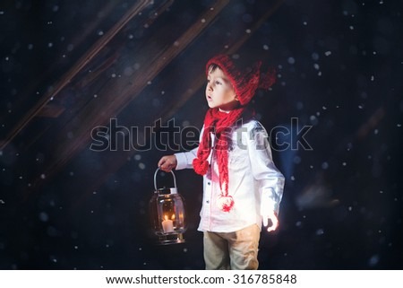 Sweet boy, holding a lantern, looking at a light coming through a window, standing in the snow, outdoors - stock photo