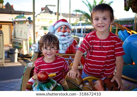Sweet boys, brothers, riding in a Santa Claus sledge on a merry-go-round, carousel attraction in Europe, active children, summertime
