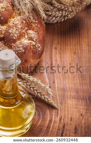 sweet bread bottle of oil wheat ears on vintage wooden board food and drink concept  - stock photo