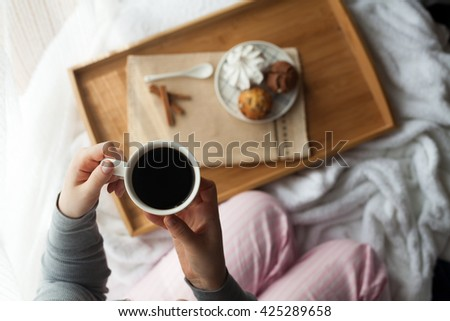 Sweet breakfast in bed with coffee set on tray, laying under sunlight. Girl drinking coffee with cupcakes. - stock photo