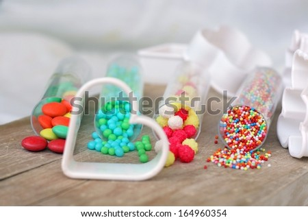 Sweet bright colored candy for children's cookies and cake decoration on wooden table with plastic white cookie cutters