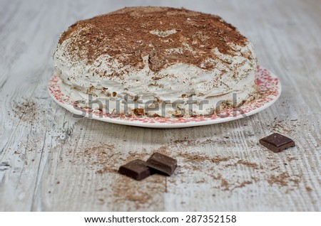 sweet brownie chocolate cream cake topped with black chocolate and cream with chocolate on wooden background - stock photo