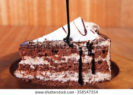 sweet brownie chocolate cream cake topped with white chocolate and cream with chocolate with chocolate sauce on wooden background - stock photo