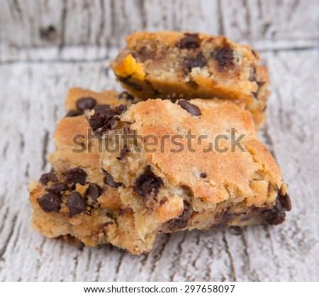Sweet brownie dessert bar with chocolate chips over wooden background