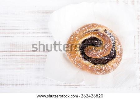 Sweet bun on white wooden background - stock photo