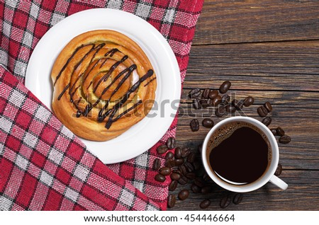Sweet bun with chocolate and cup of coffee on wooden table with red tablecloth, top view