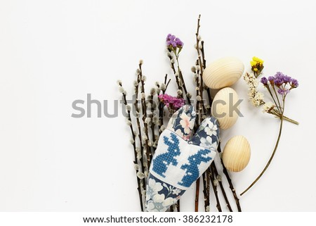 sweet bunnies on handmade floral heart and willow branches and wooden eggs on white background, holiday card concept, easter theme flatlay - stock photo