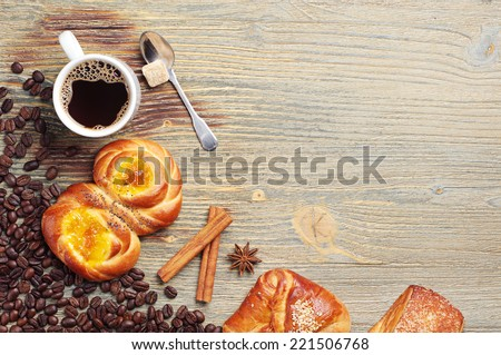 Sweet buns and coffee cup on old wooden table. Top view - stock photo