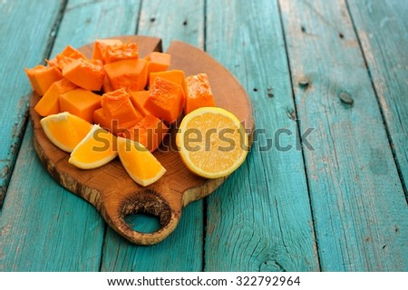 Sweet butternut squash, orange and lemon cut on wooden board on turquoise table - stock photo