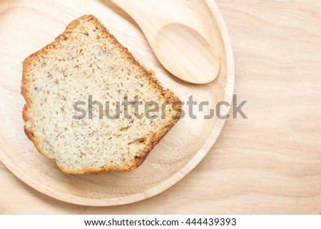 Sweet cake in wooden plate with spoon on wooden table background, Selective focus